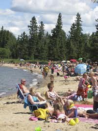 Vacationers enjoy the beach and waters of Waskesiu Lake, a popular gathering place within Saskatchewan's Prince Albert National Park.Alan Solomon