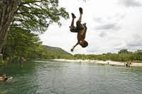 Head for the Hills -- Ralph Perez, 9, of Corpus Christi practices his backflips from a cypress tree along the Frio River at Garner State Park near Concan, Texas. Buiilt in 1941, the park leads the state in overnight camping numbers.