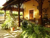Lounge chairs in shady verandahs face the gardens at Hacienda Xcanatún.
