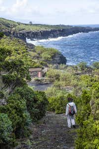 On Pico Island, guide Ana Carmo walks down a coastal path toward a building once used by early winemakers.( Phil Marty )