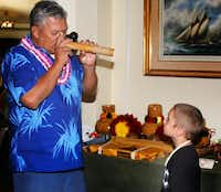 A native Hawaiian's nose flute performance fascinates a visiting boy.( Irv Green  -  Special Contributor )