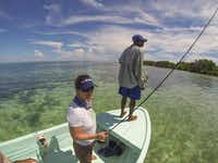 Lori Irwin and guide Lloyd Nuñez scan for bonefish, which are lightning fast and prized by anglers, on Glover's Reef.( Brian Irwin  -  Special Contributor )