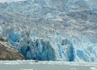 A small boat gets close to South Sawyer Glacier as the calving glacier explosively lets loose with chunks of ice.