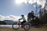 Cycling past Loch an Eilein at Rothiemurchus Estate in Cairngorms National Park near Aviemore in Inverness-shire, Scotland.