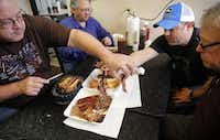 The Texas BBQ Posse dives into smoked ribs, brisket, shredded pork, and bologna during a stop Jambo's BBQ Shack in Rendon.Tom Fox  -  Staff Photographer