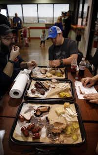 The Texas BBQ Posse dives into trays full of smoked brisket, sausage, ribs and turkey at BBQ on the Brazos in Cresson. The banana pudding made by pit master John Sanford's wife Kathryn, is the icing on the cake.Tom Fox  -  Staff Photographer