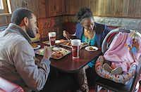 """We just moved from Nashville and didn't have anywhere to go,"" said Autumn Balfour, pictured having Thanksgiving barbecue  Thursday at the Slow Bone with husband Anthony and 5-month-old Fallon. ""This is just awesome.""( Jim Tuttle  -  Staff Photographer )"