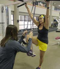 Trainer Kim Williams helps Amy Martin, 46, with the pull-up with band exercise at the Baylor Tom Landry Fitness Center. Heavy weights are incorporated into the workout.
