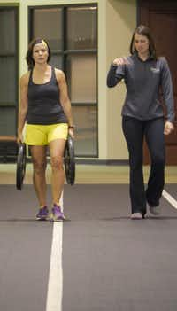Amy Martin, 46, left, performs the farmers walk carrying 45 lbs in each hand under the watchful eye of Kim Williams during her workout at the Baylor Tom Landry Fitness Center on Tuesday October 10, 2013. Heavy weights are incorporated into the workout.
