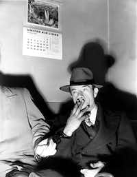 A handcuffed Willie Sutton smokes a cigarette during questioning in Queens County District Attorney's office in Long Island City, N.Y., on Feb. 18, 1952.