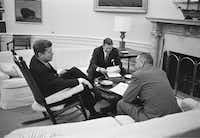 John F. Kennedy sits in his favorite rocking chair in his office during a meeting with Secretary of Defense Robert McNamara and Vice President Lyndon B. Johnson.