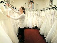 In this photo taken on Wednesday, Jan. 7, 2015, Coming Attractions Bridal & Formal Shop bridal consultant Danielle Snyder hangs a dress at the store in Akron, Ohio. Operators of the northeast Ohio bridal shop linked to an Ebola survivor say the store is closing because it lost significant business and has been stigmatized.  (AP Photo/Akron Beacon Journal, Phil Masturzo )  MANDATORY CREDIT(Phil Masturzo - AP)