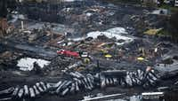 FILE - In this July 9, 2013, file photo, workers comb through debris after an oil train derailed and exploded in the town of Lac-Megantic, Quebec, killing 47 people. In response to Lac-Megantic, the National Transportation Safety Board and Transportation Safety Board of Canada in January 2014, called on regulators to require railroads to take stock of the risks along certain oil train routes and change them if needed. (AP Photo/The Canadian Press, Paul Chiasson, File)Paul Chiasson - AP