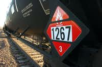 FILE - In this Nov. 6, 2013, file photo, a warning placard appears on a tank car carrying crude oil near a loading terminal in Trenton, N.D. Trains carrying millions of gallons of explosive liquids, including crude oil, are likely to continue rolling through major cities despite the governments urging to steer the shipments around population centers in the wake of several accidents, according to industry experts. (AP Photo/Matthew Brown, File)Matthew Brown - AP