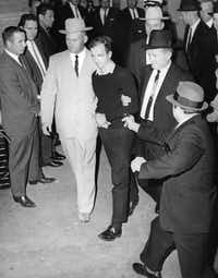 ORG XMIT: *S0407293030* FOR DALLAS MORNING NEWS 40TH ANNIVERSARY JFK THEN & NOW PACKAGE  (EMBARGOED FOR USE UNTIL SUNDAY 11/16/03 PAPERS) The accused assassin of President John F. Kennedy, Lee Harvey Oswald, center in handcuffs, is escorted to the Dallas city jail as nightclub owner Jack Ruby, foreground, approaches Oswald with a pointed revolver in the underground garage of the Dallas police headquarters, Texas, in this Nov. 24, 1963 file photo. Oswald is escorted by detectives Jim Leavelle, left, who is handcuffed to Oswald, and L.C. Graves, right.  Directly behind Graves is detective L.D. Montgomery.    MANDATORY CREDIT:  Dallas Morning News, Jack Beers [ jim leavelle - james leavelle ] / DMNstaff - DMN staff /(BEERS, jack)