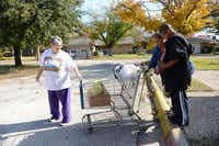 Volunteer Mary MacDonald (left) helps Linda Wooten and her grandson LaDarrian Wooten with their donated grocery items.ROSE BACA