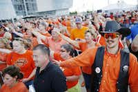 Alden Armstong (right) of Blanchard, Okla., dressed the part with an orange shirt, orange sunglasses and black vest to support his beloved Oklahoma State Cowboys during a pep rally Saturday before the Cowboys Classic at AT&T Stadium in Arlington.(Photos by Andy Jacobsohn - Staff Photographer)