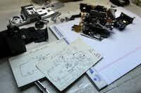 Arthur Urban, uses hand-drawn schematics as he works on a Minolta X-370 film camera at the PM Shutterworks.