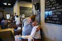 Volunteer Patricia Gosnell hugs Pedro Martinez, who is currently homeless, during lunch at Our Calling, an organization that helps the homeless through education, mentoring, recovery and resource distribution.( Rachel Woolf  - Staff Photographer)