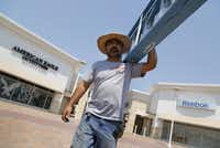 Baltazar Sanchez, a worker for Turner Sign Systems, finishes installing a sign at the Paragon Outlets in Grand Prairie.