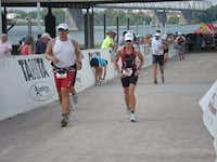 Hoffman (right) runs the last leg of the 2010 Louisville Ironman triathlon after swimming 2.4 miles and biking 112 miles.Photo submitted by CARLA HOFFMAN