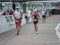 Hoffman (right) runs the last leg of the 2010 Louisville Ironman triathlon after swimming 2.4 miles and biking 112 miles.(Photo submitted by CARLA HOFFMAN)