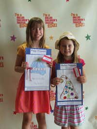 Paige Hounsel (left) and Hailey Duggan hold their designs for 'Twas the Night Before Christmas at the Dallas Children's Theater's hat winner announcement party.