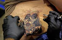 Chicago-based artist Angel Silva tattooed Daniel Martinez of Granbury at the festival Sunday.(G.J. McCarthy - Staff Photographer)