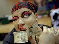 "Sandra ""BZ"" has cash stapled to her face as part of a performance by the Captain's Sideshow of Oklahoma City.(G.J. McCarthy - Staff Photographer)"