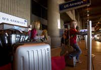 Mireille Hayzlett, 6, and her brother, Nolan, 8, of Scottsdale check in at Sky Harbor International  Airport with their parents for a US Airways flight.