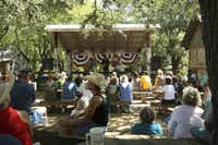 Oak trees arch over a crowd at the Picker Circle listening to country music in Luckenbach, Texas.