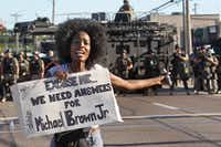 A protester shouts as she moves away from a line of riot police in Ferguson, Mo. on Wednesday, Aug. 13, 2014. On Saturday, Aug. 9, 2014, a white police officer fatally shot Michael Brown, an unarmed black teenager, in the St. Louis suburb. (AP Photo/St. Louis Post-Dispatch, J.B. Forbes)J.B. Forbes - AP