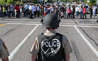 A line of police wait for demostrators at Canfield Avenue after they had walked down W. Florissant in Ferguson, Mo. on Wednesday, Aug. 13, 2014. On Saturday, Aug. 9, 2014, a white police officer fatally shot Michael Brown, an unarmed black teenager, in the St. Louis suburb. (AP Photo/St. Louis Post-Dispatch, J.B. Forbes)J.B. Forbes - AP