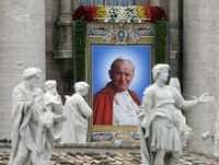The tapestry showing Pope John Paul II hangs from the facade of St. Peter's Basilica during a solemn celebration led by Pope Francis I where two Popes, John Paul II  and John XXIII, were canonized, in St. Peter's Square at the Vatican, Sunday, April 27, 2014. (AP Photo/Alessandra Tarantino)Alessandra Tarantino - AP