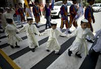 Children dreesed as Pope John Pauil II participate in a parade in Manila on April 27, 2014, as millions around the world celebrate the cannonisation of John Paul II and John XXIII. Catholics from around the world gathered in Rome for a mass presided by Pope Francis to confer sainthood on John Paul II and John XXIII -- two influential popes who helped shape 20th century history. AFP PHOTO/NOEL CELISNOEL CELIS/AFP/Getty ImagesNOEL CELIS - AFP/Getty Images