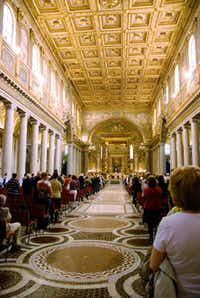 Regular worshippers and visitors alike attend mass at Santa Maria Maggiore, one of Rome's four major churches. The ceiling is thought to be covered in gold that Christopher Columbus brought back from the Americas.