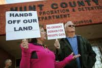 Kathy Carrell and her husband Mike Carrell from Caddo Mills, Texas holds a sign in protest of the Northeast Gateway toll road at Hunt County Commissioners Court, Auxiliary Courtroom in Greenville, Texas October 14, 2014.
