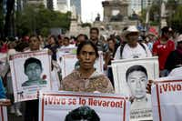 Marchers went through  the streets of Mexico City in August carrying banners bearing pictures of some of the 43 students who disappeared in southern Guerrero state in 2014. The case remains unsolved.File Photo - The Associated Press