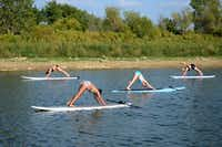 Local residents do paddleboard yoga on Lake Lewisville. Paddleboard yoga came to Lewisville Lake just this year, after Natalie Tailford's Float on Yoga business began in 2011 on Grapevine Lake. The practice of standup paddleboard yoga originated in Hawaii and is spreading fast across the U.S. There are now dozens of classes across Texas, but Float on Yoga claims to the first in North Texas.