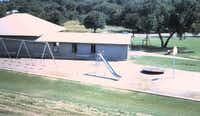 A 1970s photo shows the recreation center and playground equipment at Oak Cliff Park, which was created in 1915 as one of the city's first parks for black residents.