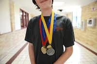 Eighth-grader Ryan Mann poses for a portrait with his Pentathlon medals at Austin Academy for Excellence in Garland, Texas on June 3, 2014. The eighth and seventh grade teams won first and second place, respectively, at the Academic Pentathlon competition May 23-24 in Omaha, Nebraska.( Rose Baca  -  neighborsgo staff photographer )