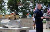 Cpl. J.R. Podany of the Cedar Hill Police speaks to attendees next to a statue of his partner Titus, a Belgian Malinois and member of the Cedar Hill K-9 Unit, at the Cedar Hill Pet Memorial Park during a recent ceremony honoring service pets.(Staff photos by ROSE BACA - neighborsgo staff photographer)