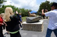 Attendees take photos of the War Dog memorial at Cedar Hill Pet Memorial Park. Plots are available to military and law enforcement service animals at no cost.(Rose Baca - neighborsgo staff photographer)