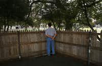 A tourist views the JFK assassination site from behind a graffiti-covered fence atop the grassy knoll.