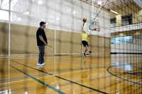 Michael Dalby jumps to paddle the ball during a round of pickleball, while teammate Ronnie Curry looks on. During the day, the basketball courts at the Cedar HIll Recreation Center are used for pickleball.ROSE BACA/neighborsgo staff photographer