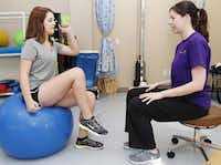 Physical therapist Lara Trevett (right) leads Haley Holmes, 16, in a hip and core exercise at Children's Health Specialty Center at the Southlake location. Holmes, a high school athlete, has been receiving physical therapy treatments for about three months for a Sacroiliac Joint misalignment stemming from playing volleyball.( Photo by Brandon Wade  -  special contributor )