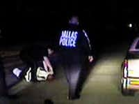 Dallas police officer Quaitemes Williams (bent over on left) faces a criminal charge after he was caught on video kicking a handcuffed prisoner in the head and using pepper spray on him.