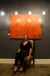 """Susan Bishop sits next to her piece """"Chili Hot Red."""" Bishop, a local artist and planning committee member of the Pop Up exhibit, is helping put local art into the spotlight."""