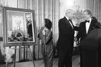 President Jimmy Carter shakes hands with the manager of his unsuccessful re-election campaign at a White House reception in Washington on Dec. 9, 1980. Mrs. Robert Strauss examines the Norman Rockwell painting the president presented to Strauss,( Dennis Cook  -  ASSOCIATED PRESS )