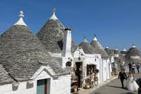 A bride and  groom traverse the streets of picturesque Alberobello, Italy, with a photo-grapher after their wedding ceremony.(Amy Laughinghouse - Special Contributor)